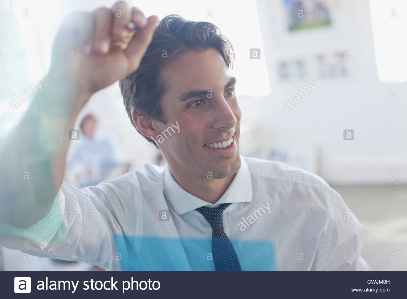 Smiling businessman leaning against glass in office Photo Stock