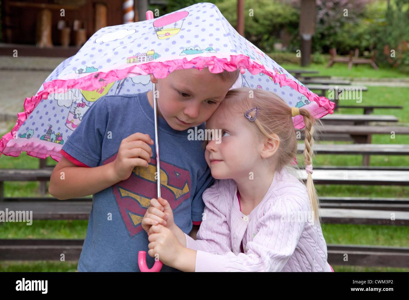 Aimer les frères et sœurs des enfants garçon et fille de 6 et 4 sous un parasol. Spala Centre de la Pologne Photo Stock