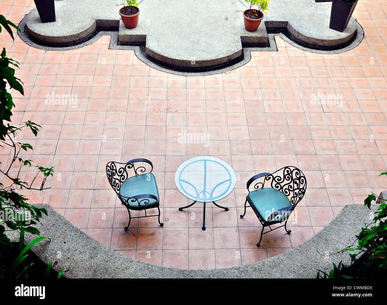 Deux chaises de jardin contre le mur de brique Banque D'Images