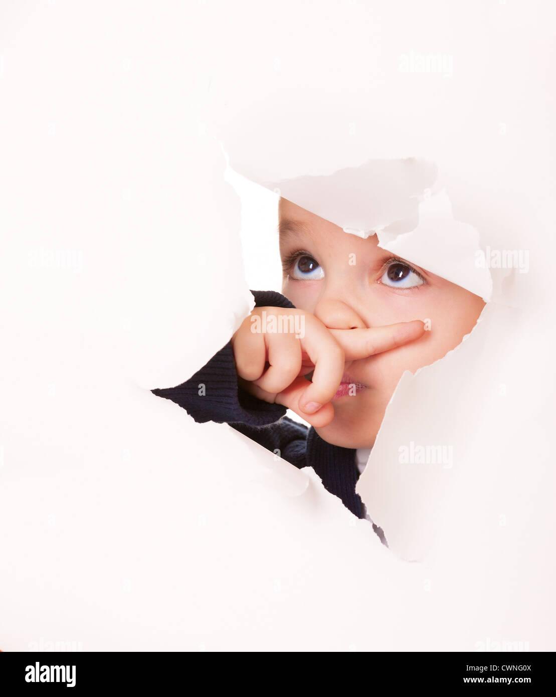 Coupable kid regarde par un trou dans du papier blanc Photo Stock
