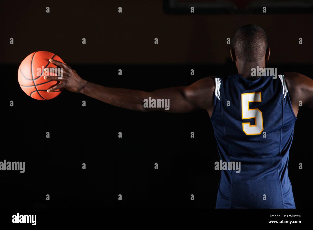 Basket-ball Basket-ball joueur tenant en main, vue arrière Photo Stock