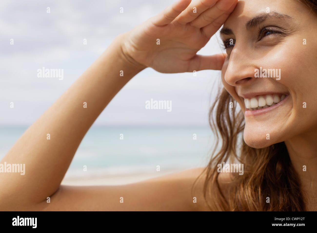 Femme à la plage, l'ombrage des yeux pour regarder voir Photo Stock