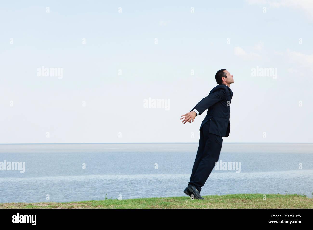 Businessman debout sur la pointe des pieds par la mer, en prenant une profonde respiration Banque D'Images