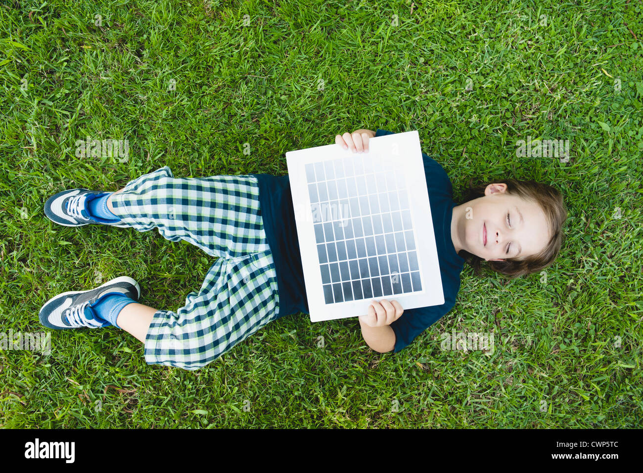 Boy lying on grass holding solar panel Photo Stock