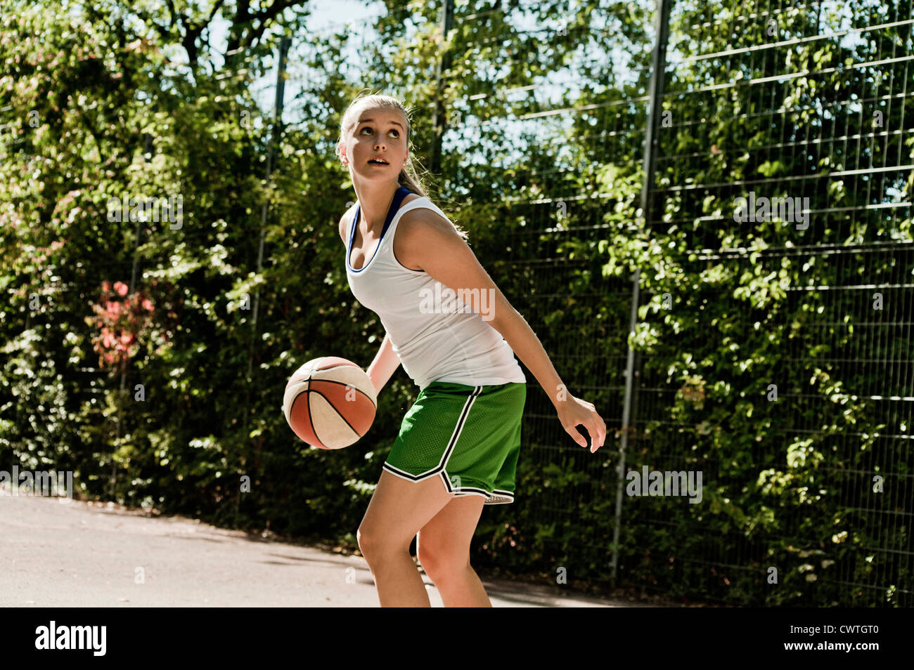 Teenage girl playing basketball Photo Stock