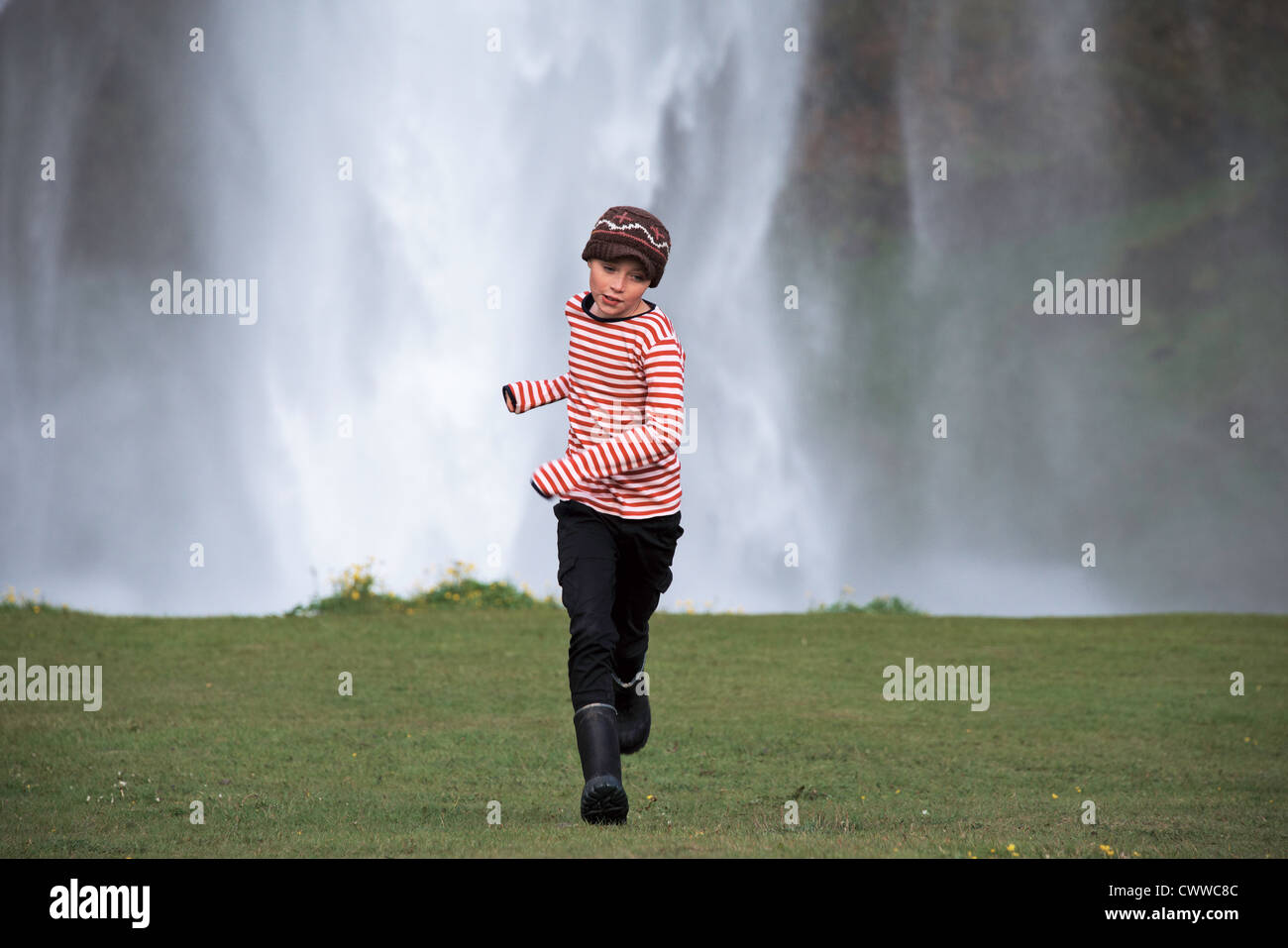 Girl running in grassy field Photo Stock