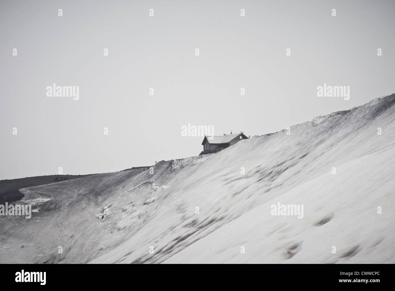 Maison construite sur une colline de neige Photo Stock