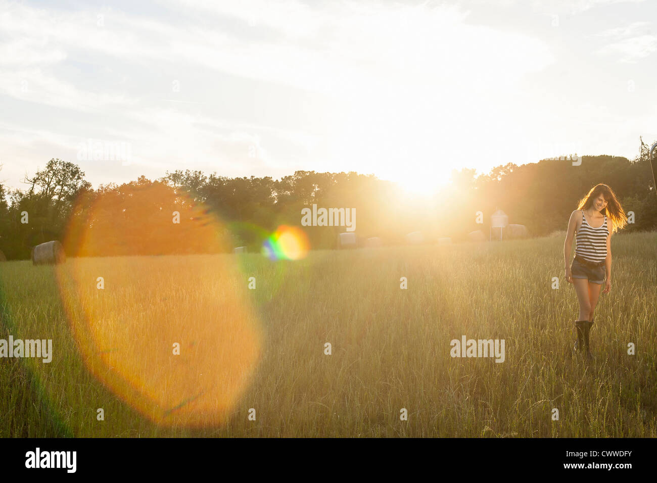 Smiling woman walking in grassy field Banque D'Images