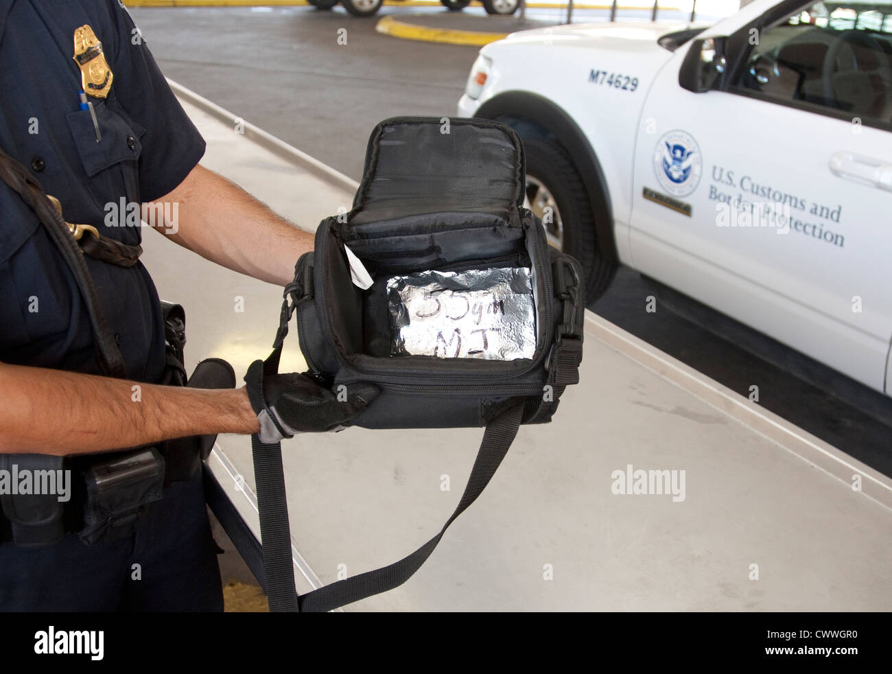 U.S Customs and Border Protection Élections ouvre sac contenant un paquet de marijuana, de former des chiens Photo Stock