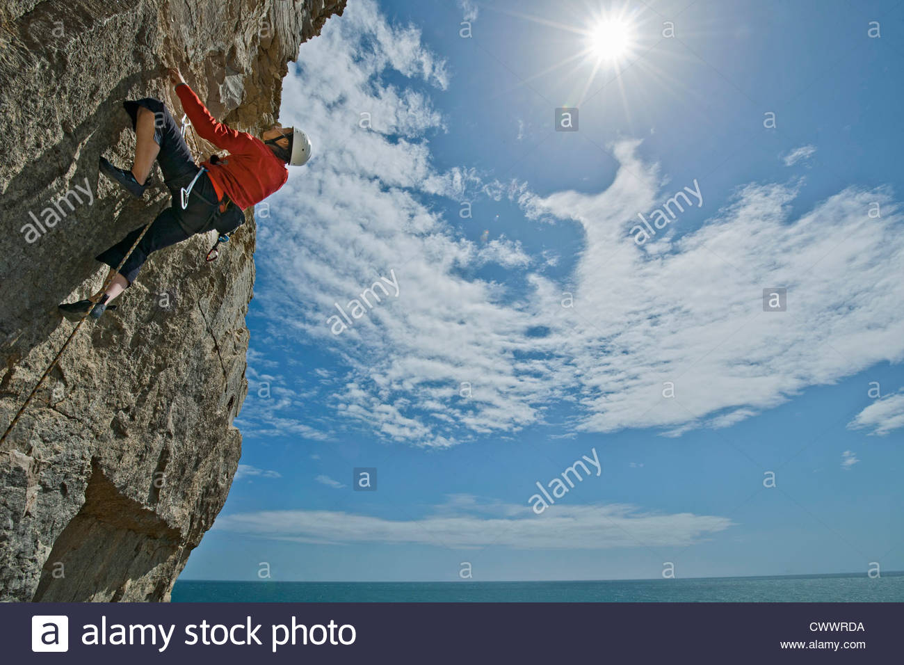 Climber scaling steep cliff face Photo Stock