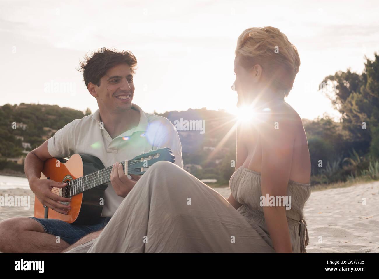 L'homme qui joue de la guitare pour l'amie Photo Stock