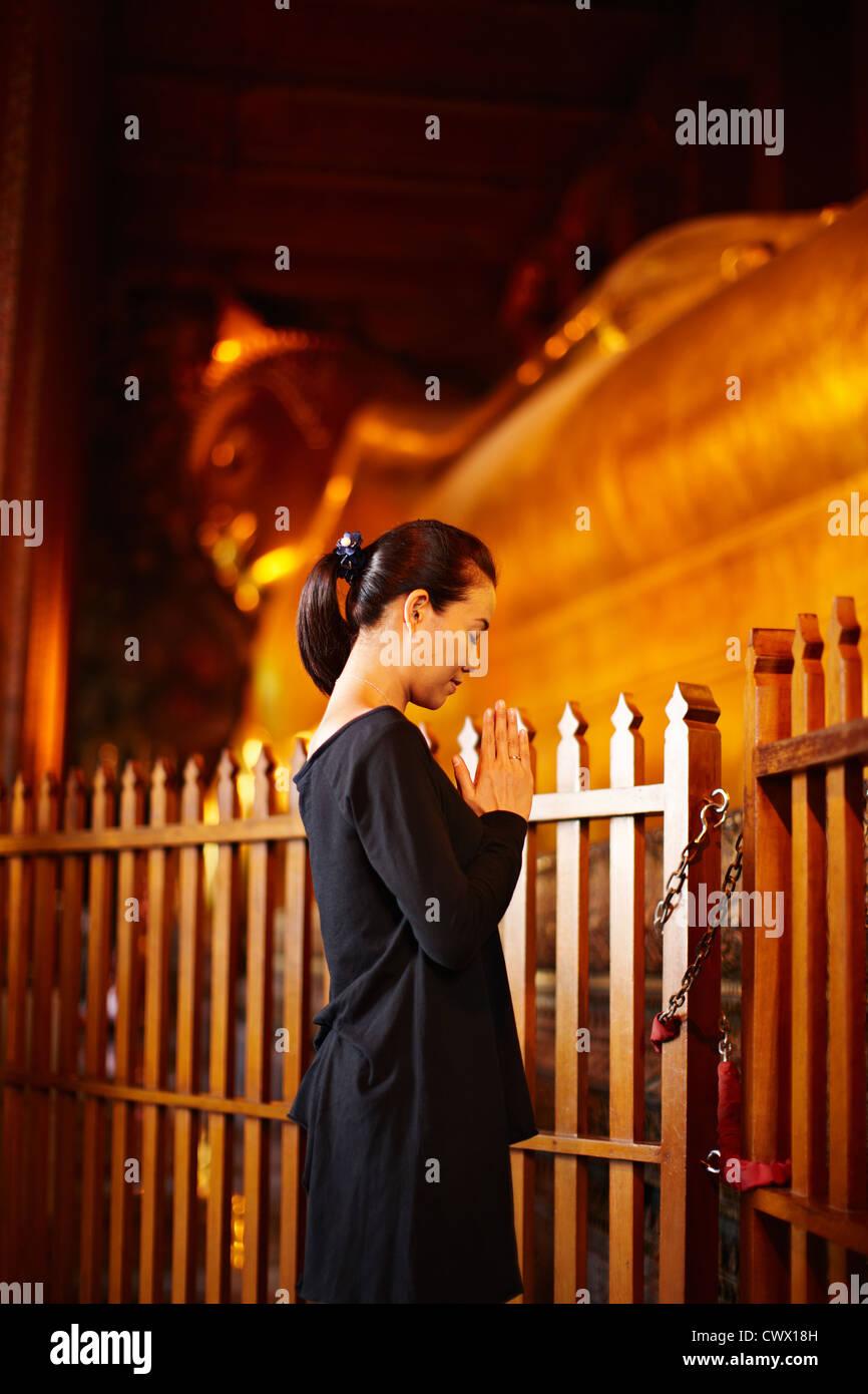 Femme en prière à monument en plein air Photo Stock