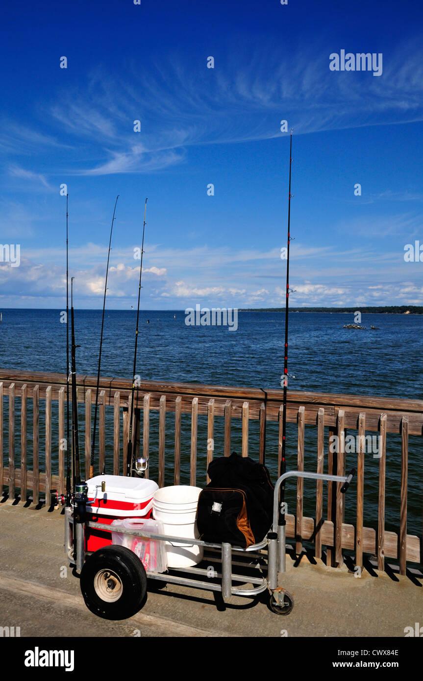 Panier avec tiges, bobines et les articles de pêche sur la jetée de Owego Photo Stock