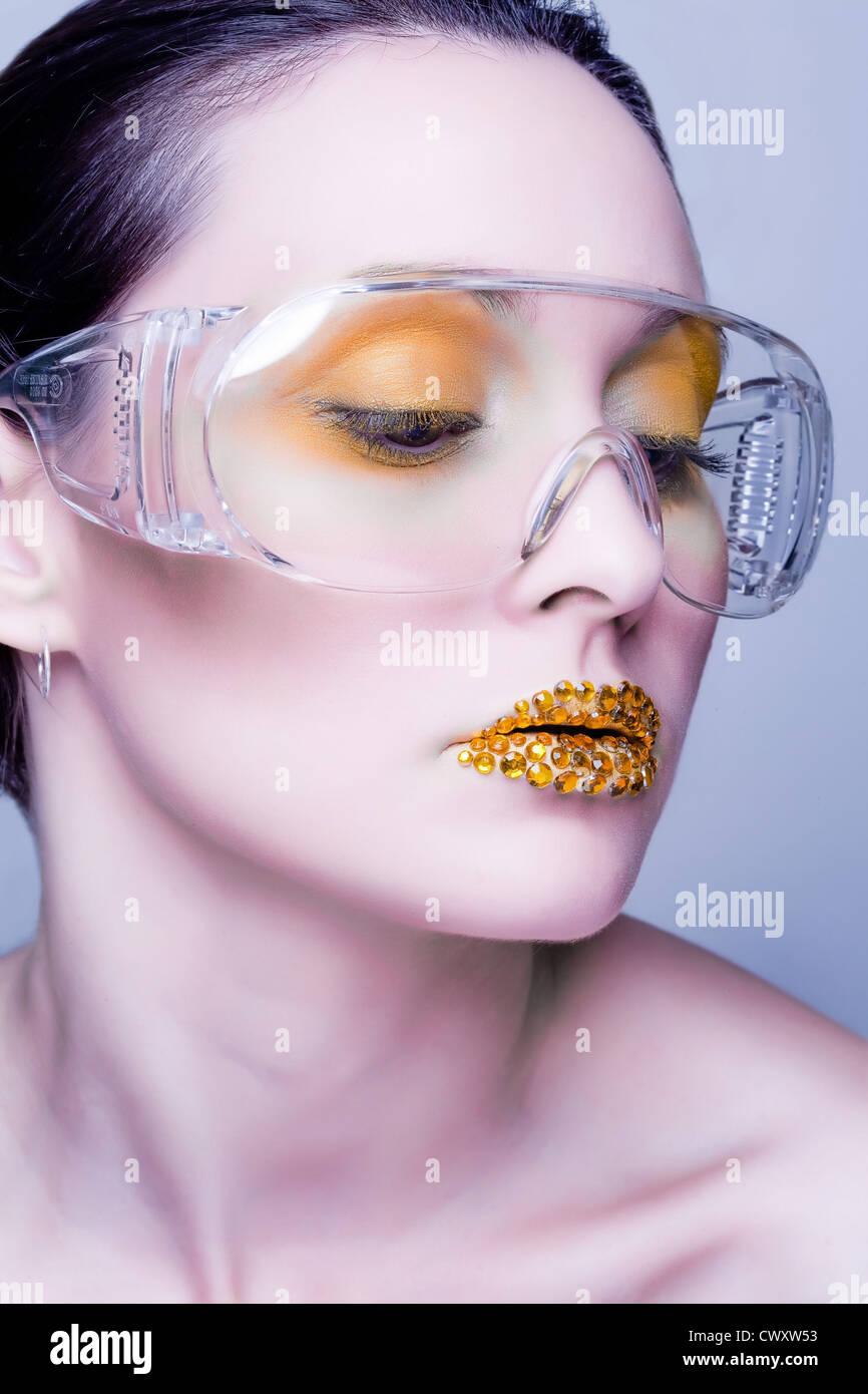 Young caucasian woman with gold fashion makeup portant des lunettes claires et or diamonties sur ses lèvres Photo Stock