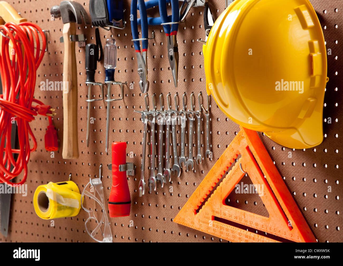 Une plaque avec divers outils tels que: marteau, scie, clés, lampe de poche, rallonge, tournevis Banque D'Images