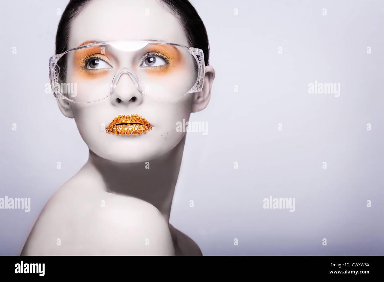 Young caucasian woman with gold fashion makeup portant des lunettes claires et or diamonties sur ses lèvres Banque D'Images