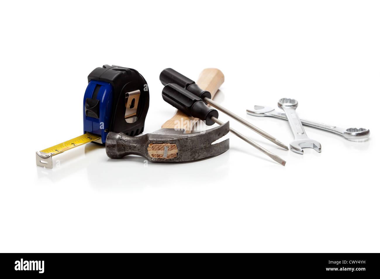 Outils divers y compris d'un marteau, ruban à mesurer Tournevis et clés sur un fond blanc Banque D'Images