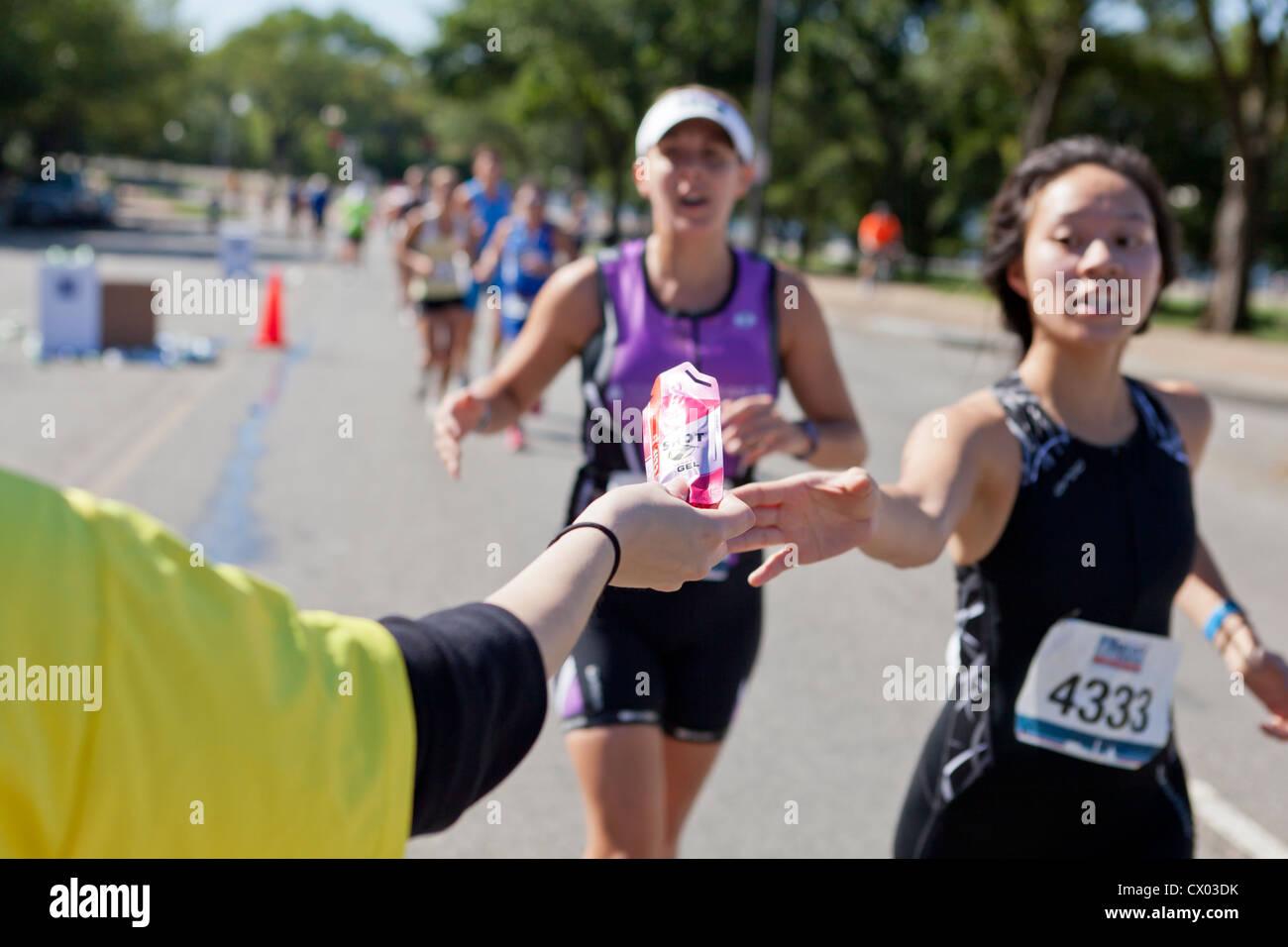 Coureur de marathon d'atteindre pour un paquet de gel énergétique - USA Photo Stock