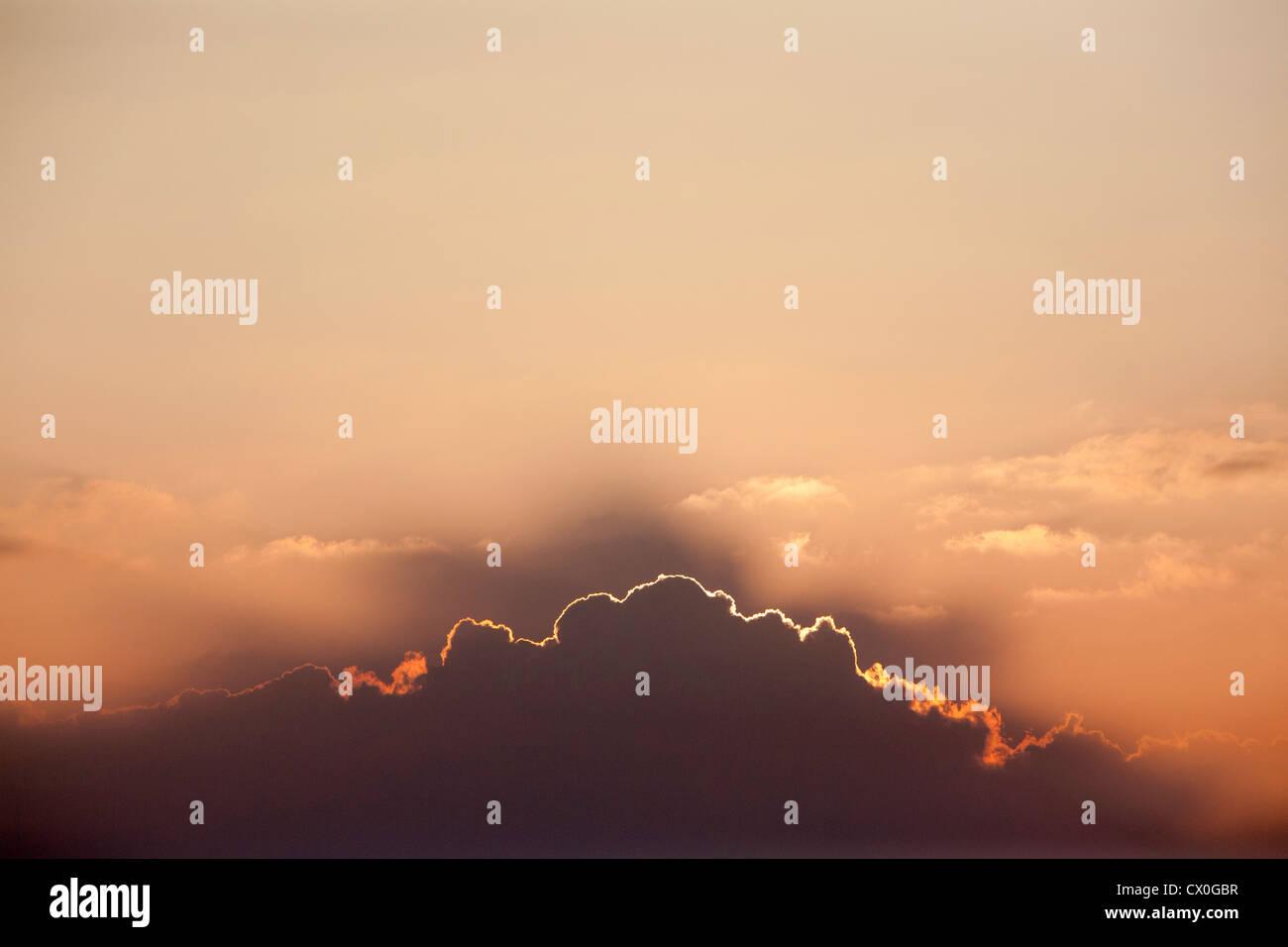 Doublure d'argent à mesure que le soleil disparaît derrière une ligne de nuages Photo Stock