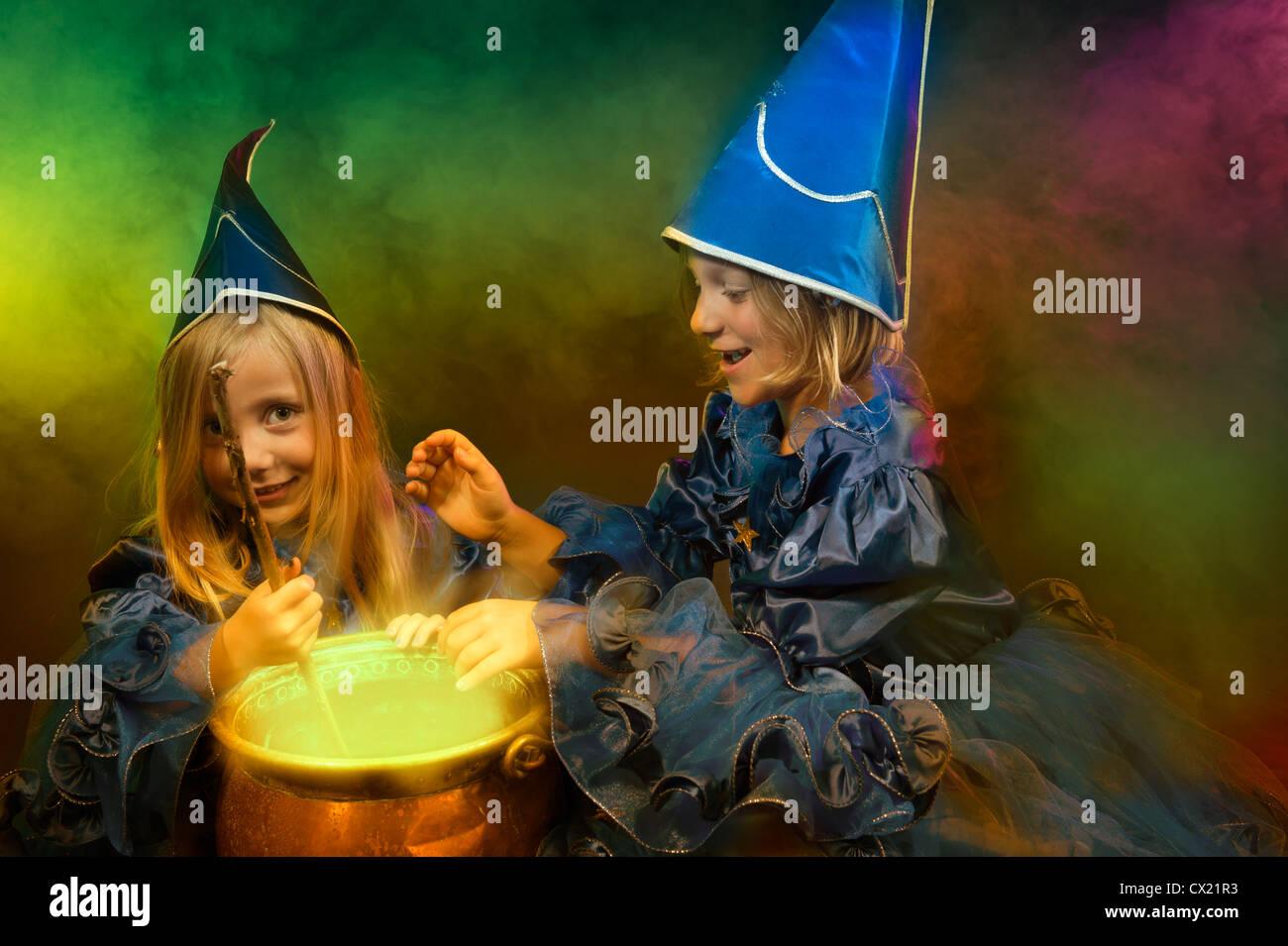 Deux petites sorcières halloween avec chaudron Photo Stock