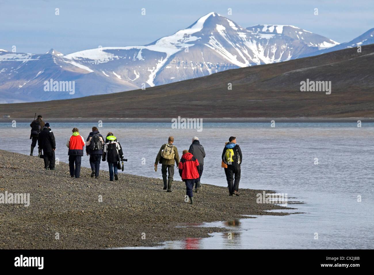 Les touristes walking on beach le long de Tempel Fjord avec guide armé d'un fusil contre les ours polaires Photo Stock