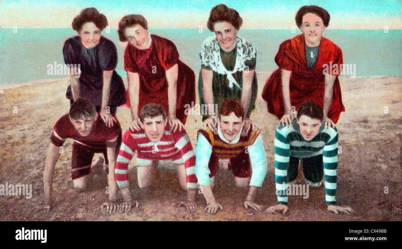 Fun sur la plage - Vintage postcard de jeunes hommes et femmes jouant sur la plage Photo Stock