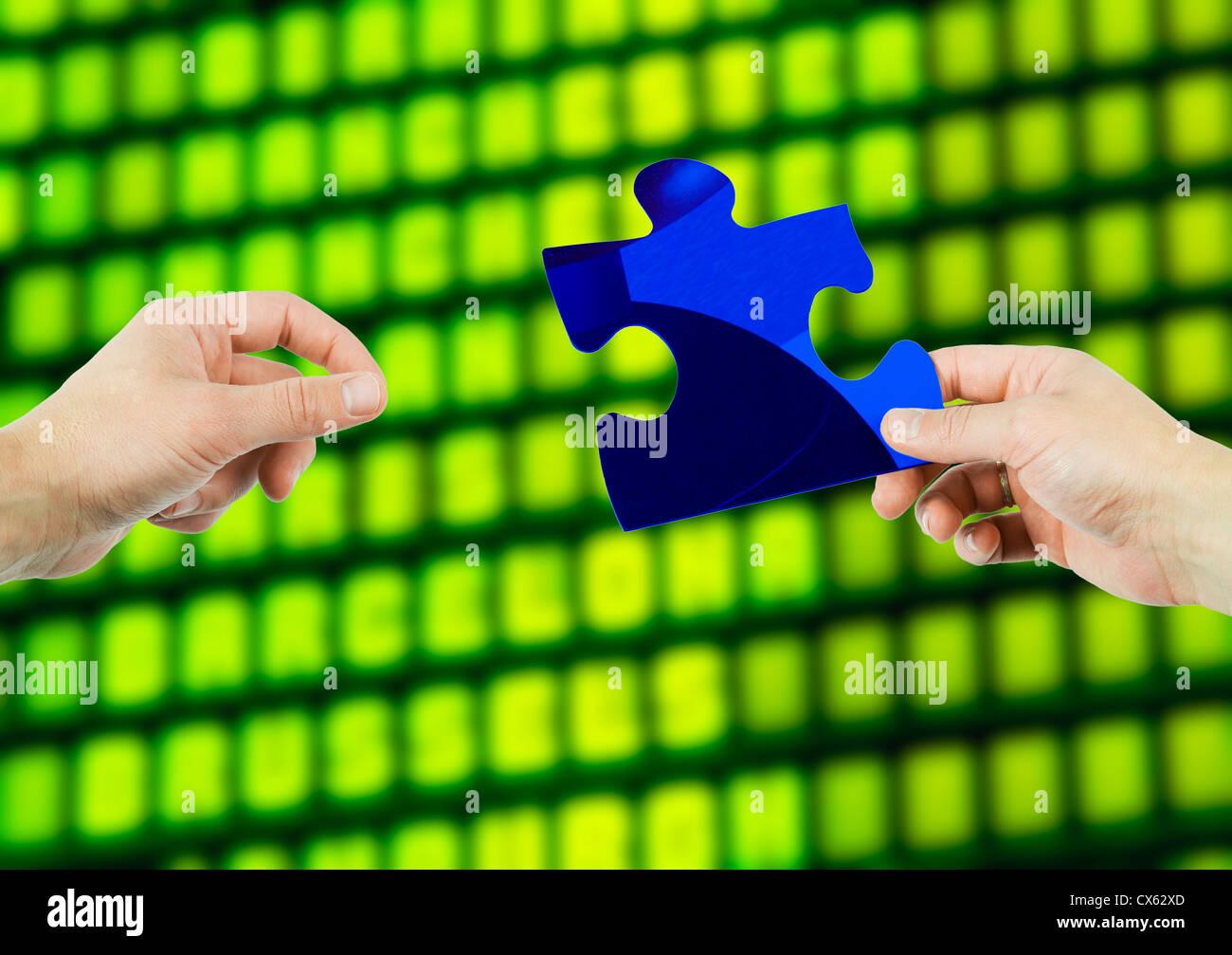 Une main s'étendant sur des pièces d'un puzzle qui s'est tenue par une autre main Photo Stock