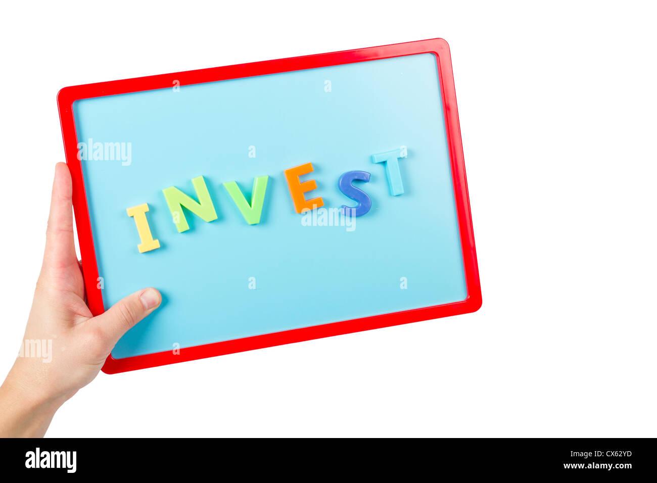 Mot 'Investir' énoncées avec des lettres magnétiques sur un mini tableau magnétique. Photo Stock