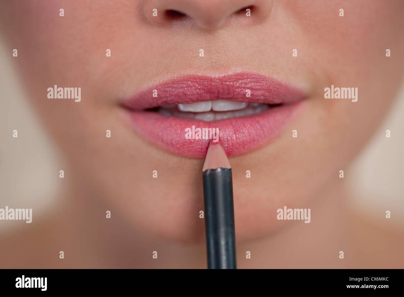 Une jeune femme l'application de recouvrement de lèvre, montrant la partie inférieure de la face Photo Stock