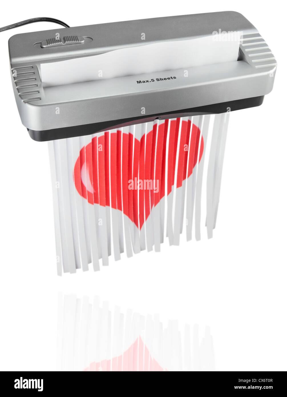 Une déchiqueteuse électrique qui déchiquette un papier rouge coeur. Copier l'espace. Isolées. Banque D'Images