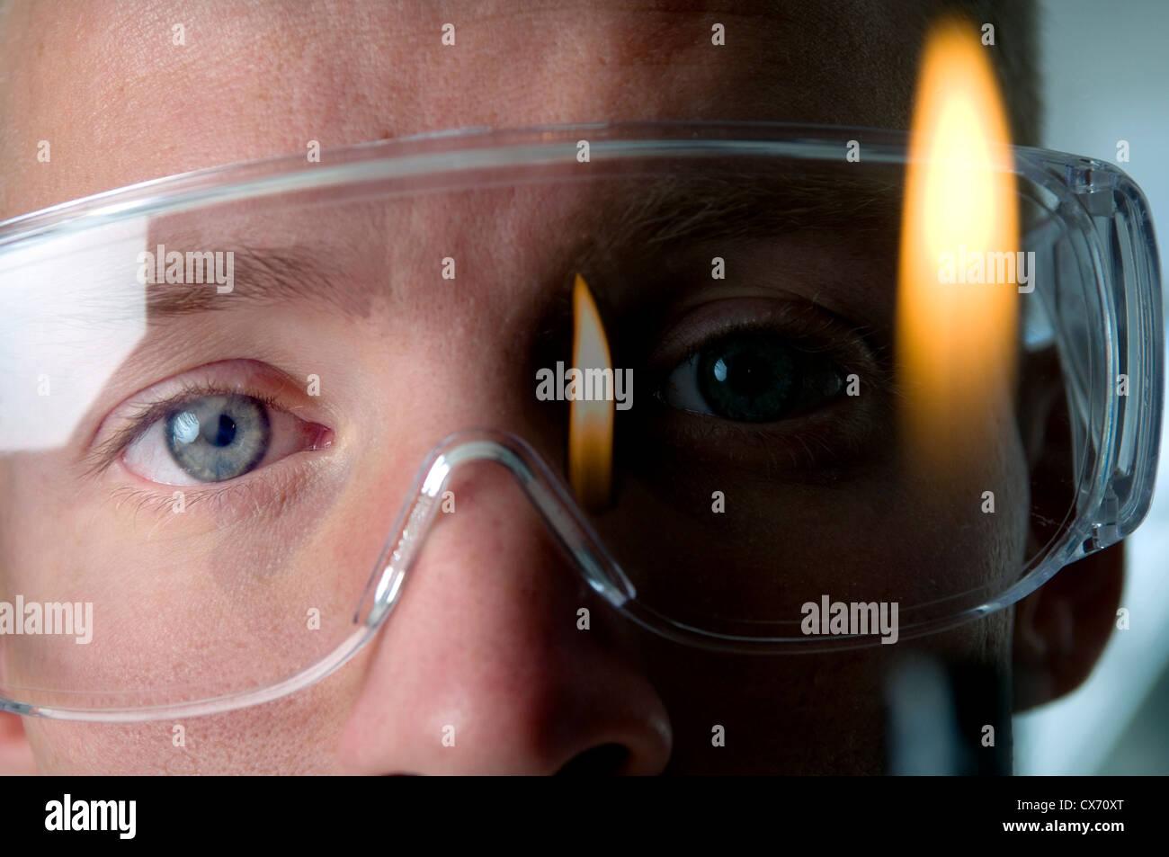 Jeune homme étudiant/chercheur scientifique en face de la flamme Bunsen Photo Stock
