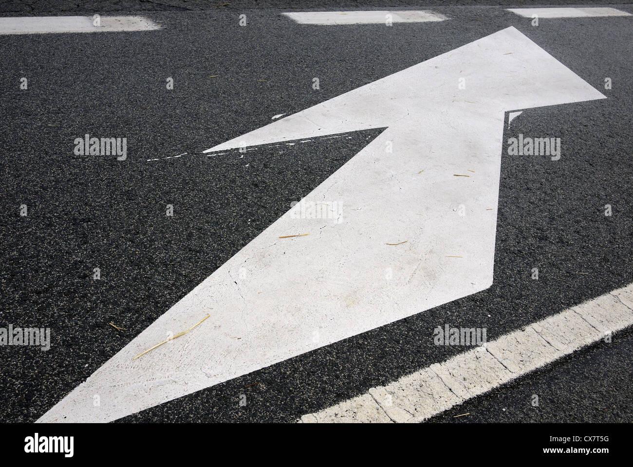 Flèche blanche peinte sur une route. Photo Stock