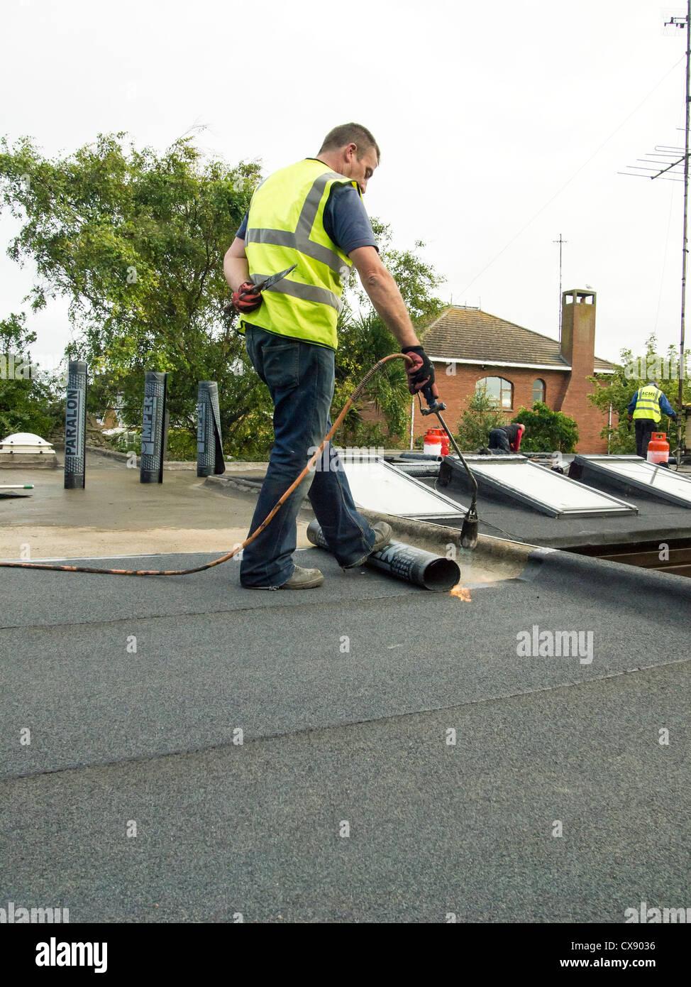 Un ouvrier portant une torche sur l'impression revêtement de toiture sur un toit plat. Photo Stock