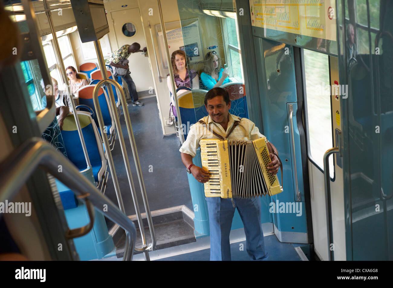 Un homme rom ou tsigane de la rue dans un train entre Paris et Versailles avec un accordéon Banque D'Images