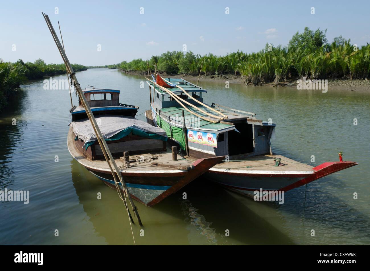 Bateaux dans une voie navigable avec arbres de mangrove, Delta de l'Irrawaddy, le Myanmar (Birmanie), l'Asie Photo Stock