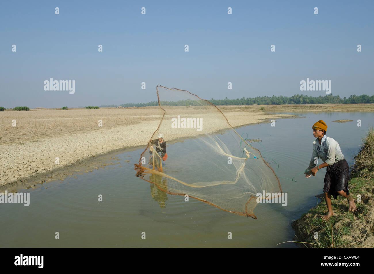 Jeune pêcher avec filet de pêche dans un cours d'eau, delta de l'Irrawaddy, le Myanmar (Birmanie), Photo Stock