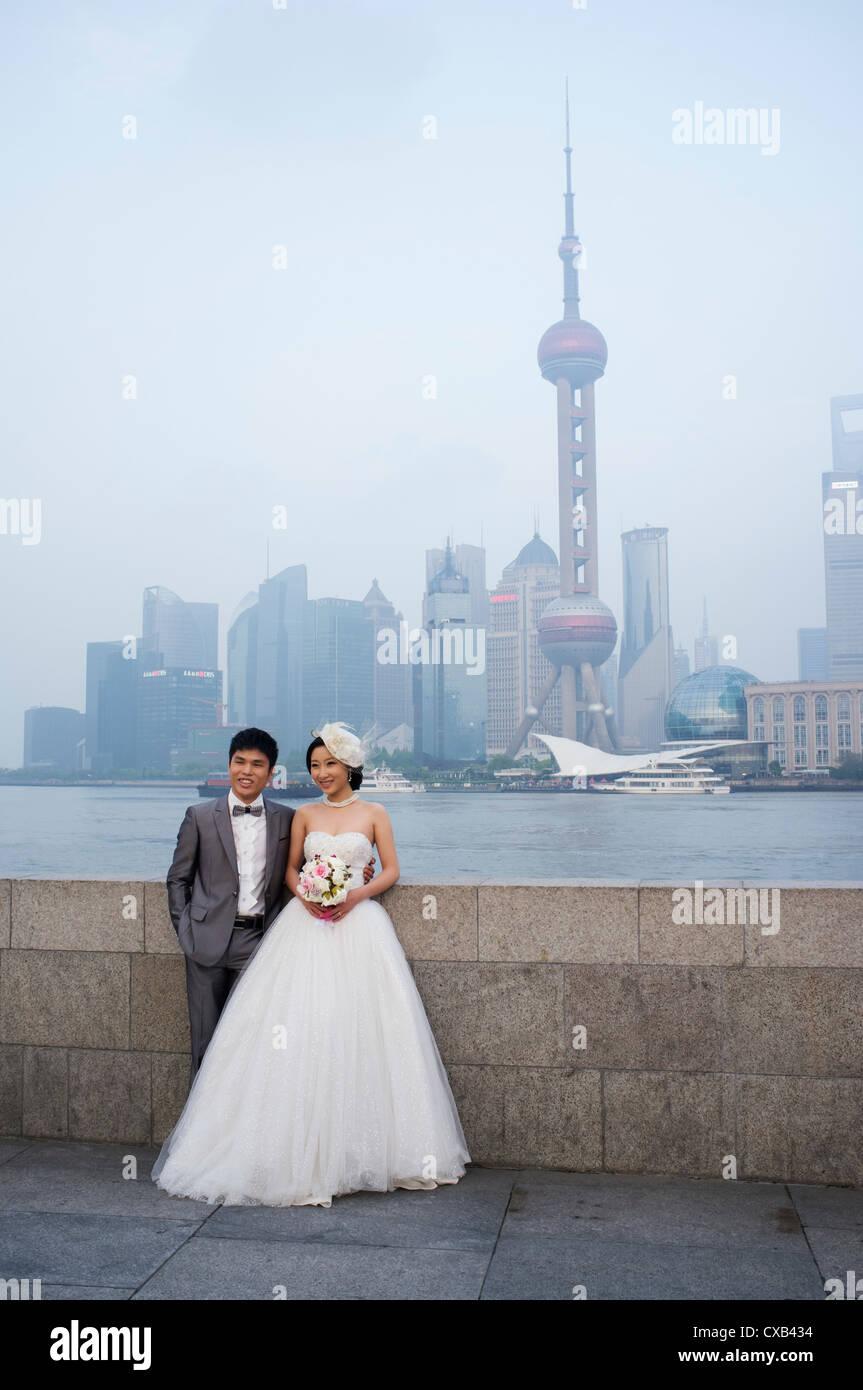 Deux jeunes mariés qui pose pour les photographies de mariage sur le Bund avec le quartier financier de Pudong Photo Stock