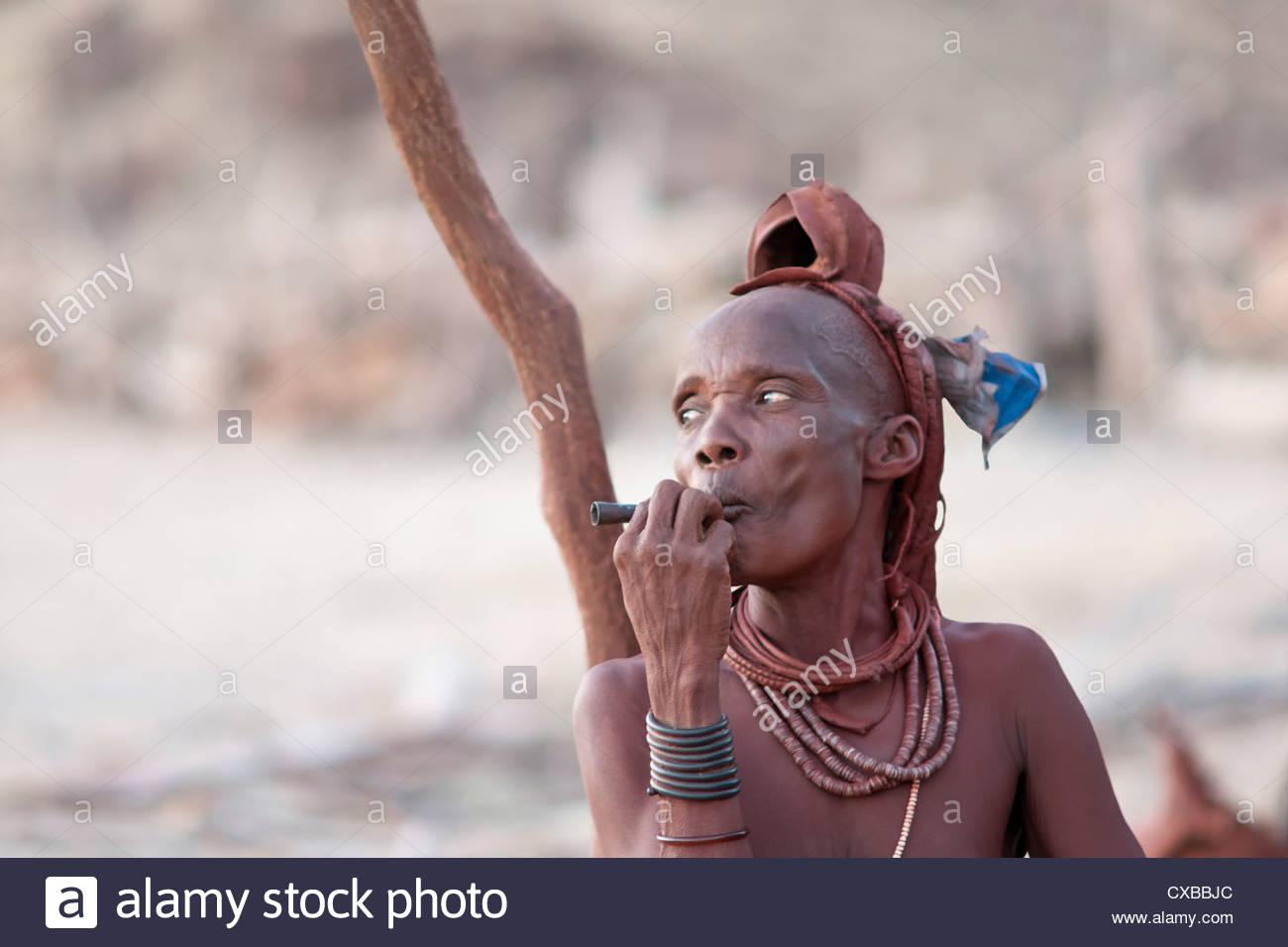 Femme Himba fume à l'extérieur de sa maison au toit de chaume dans le petit village, Purros, Namibie, Photo Stock