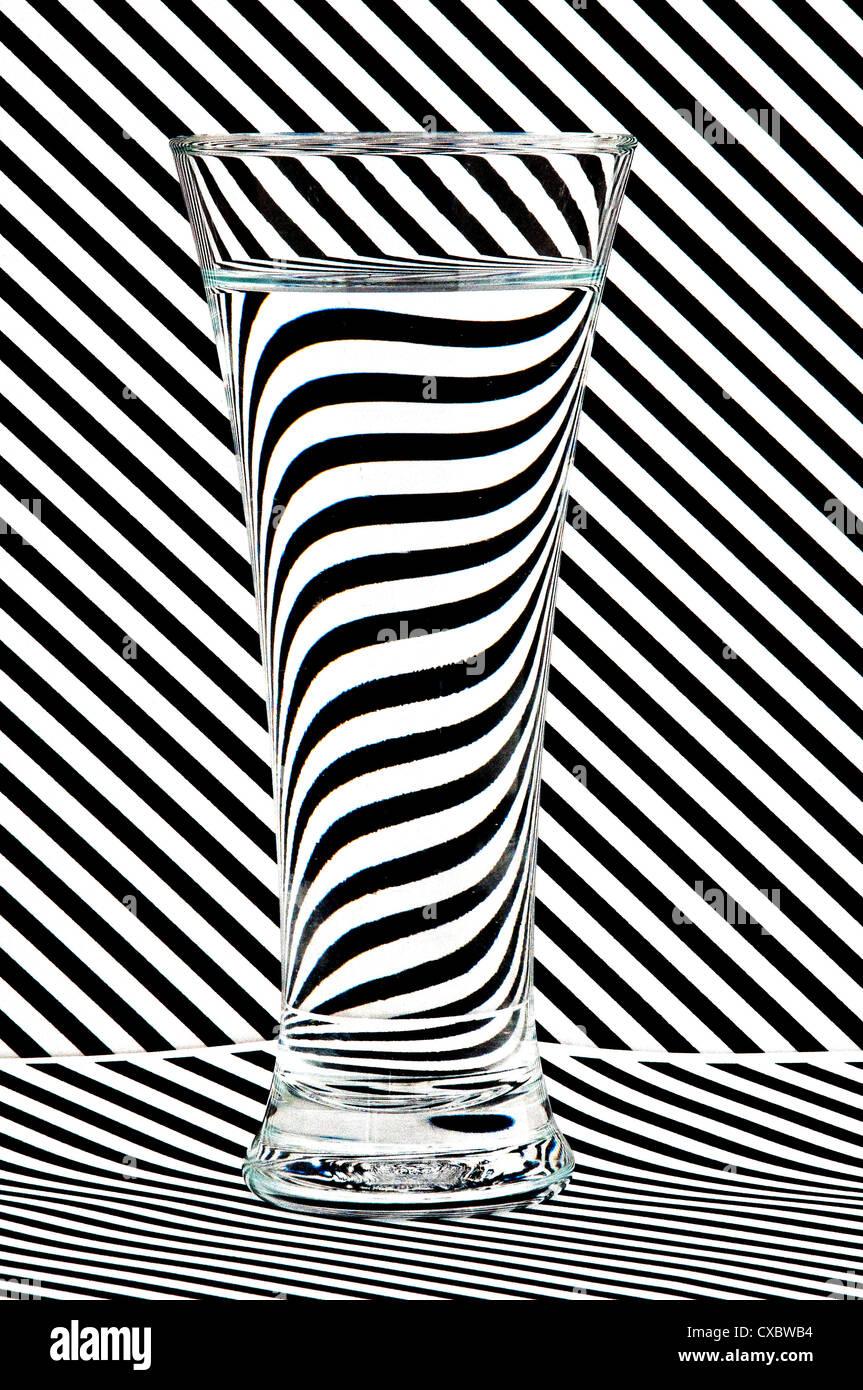 C'est un verre d'eau tiré contre un arrière-plan pour illustrer l'effet de l'eau en réfractant Photo Stock