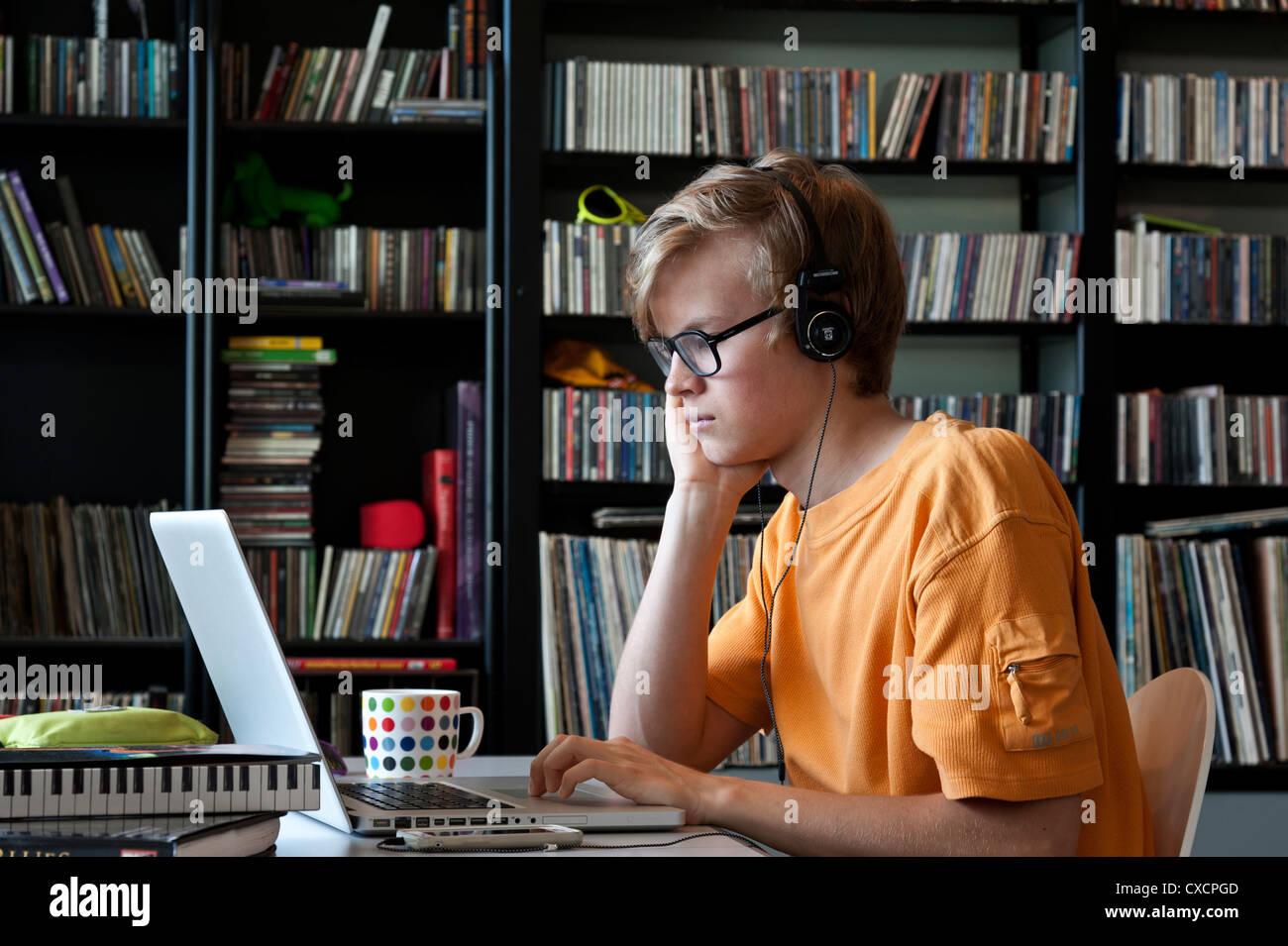 Teenage détendue studieux garçon portant des écouteurs à l aide de son ordinateur  portable Photo 71e703b732a4