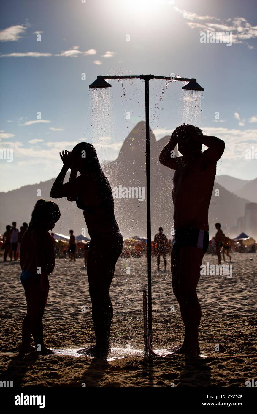 Profitez de la famille douche rafraîchissante à la plage d'Ipanema, Rio de Janeiro, Brésil. L'été Photo Stock