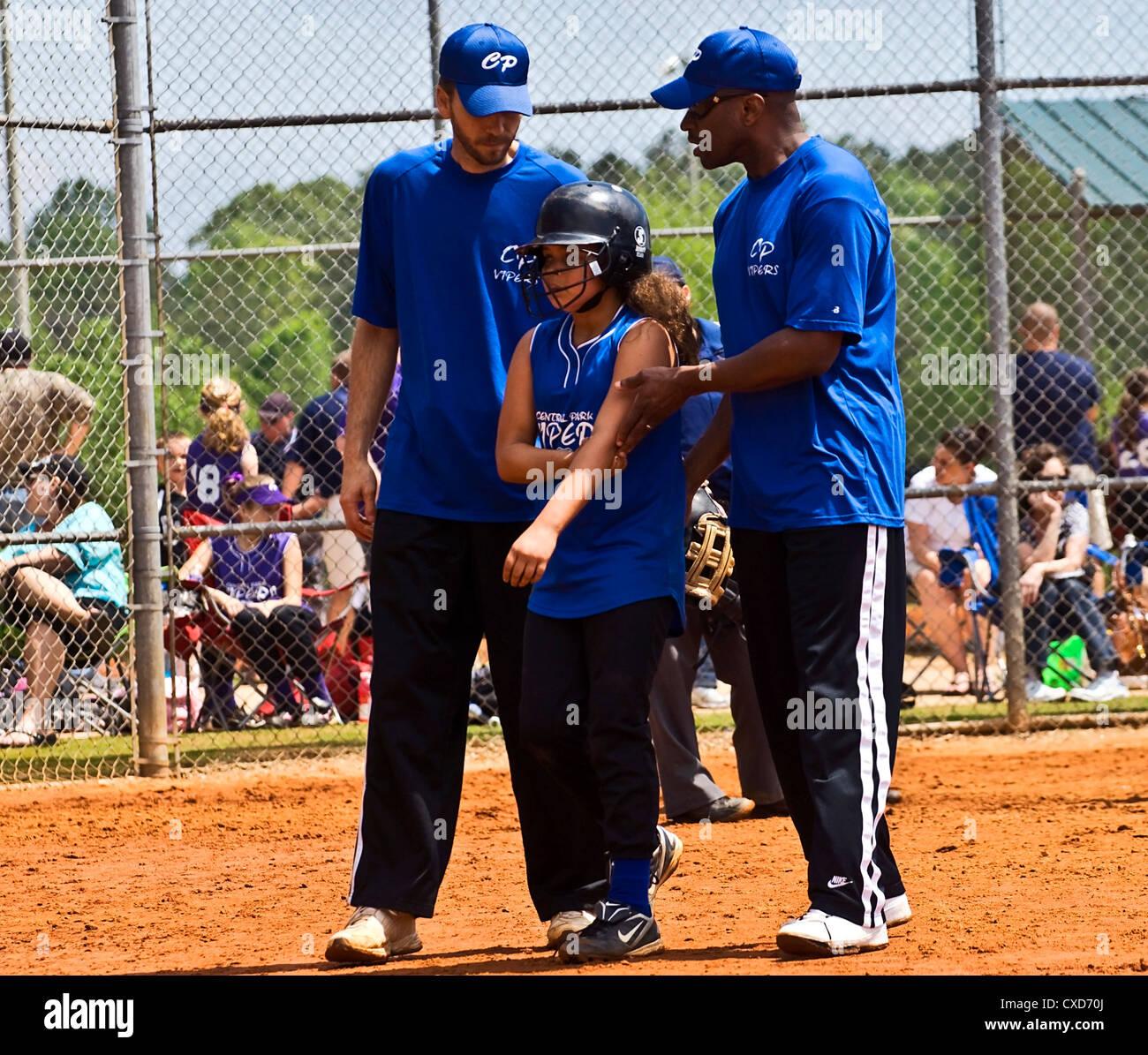 Jeune joueur de baseball étant pris en charge par les entraîneurs après une blessure. Photo Stock