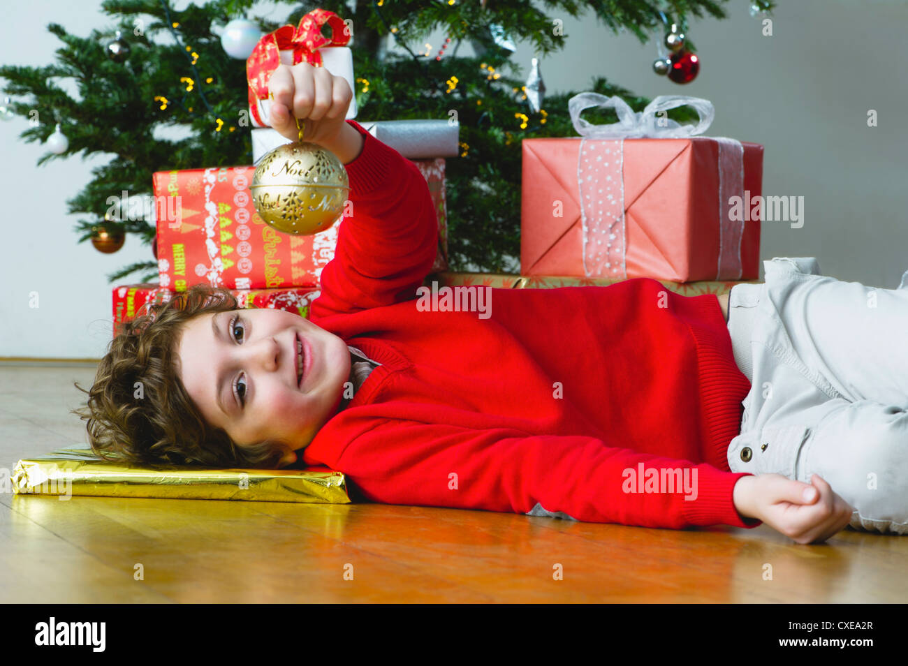 Boy lying on floor by Christmas Tree, holding up ornament Photo Stock