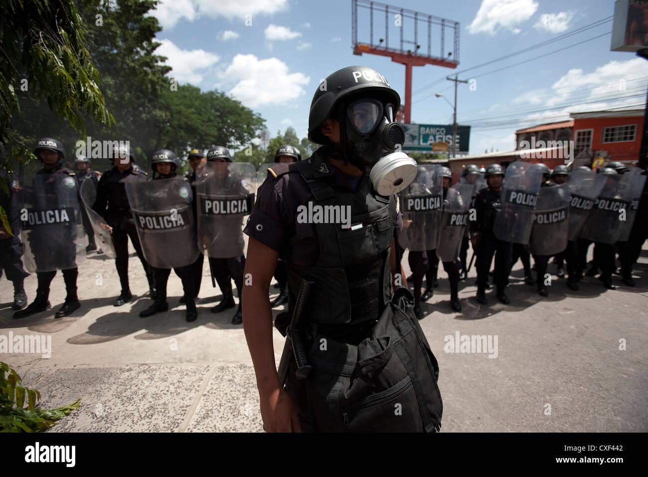 La police hondurienne montent la garde comme des milliers de partisans du Président déchu du Honduras Manuel Zelaya protester à Tegucigalpa Banque D'Images