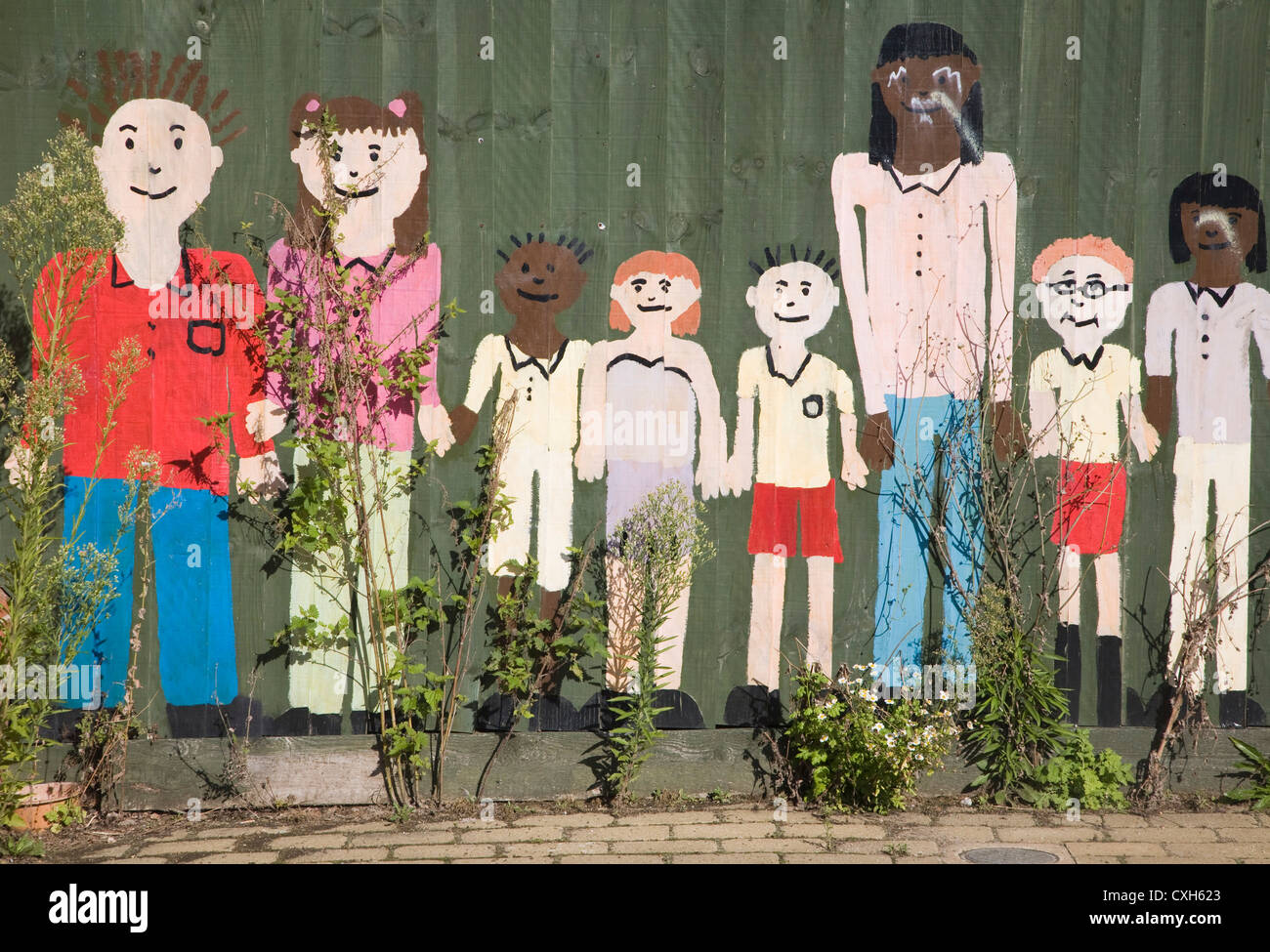 Figures peintes d'école maternelle les enfants mur de clôture Banque D'Images