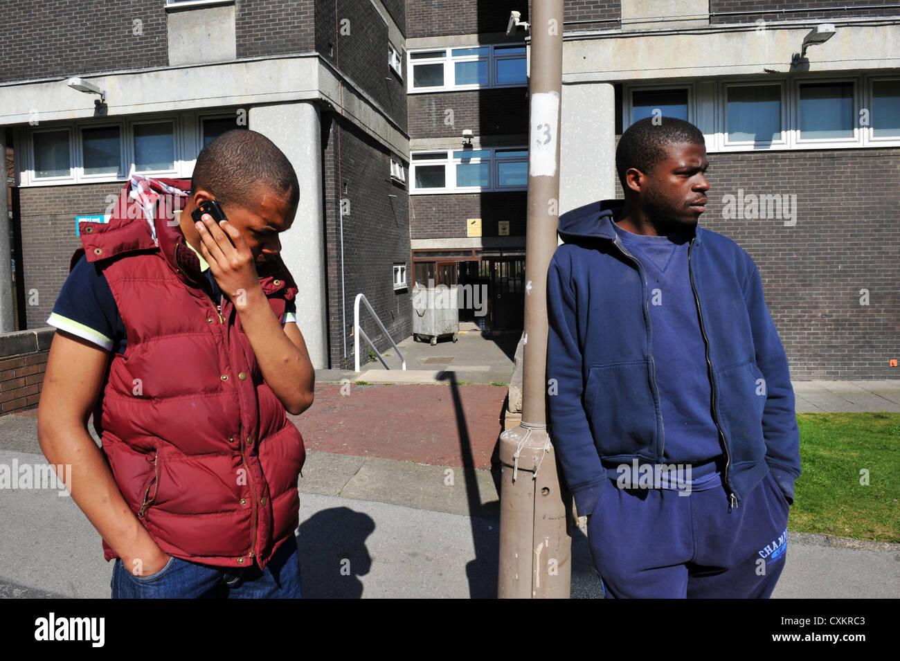 Deux jeunes Jeunes chômeurs Leeds UK, l'un parlant au téléphone. Banque D'Images