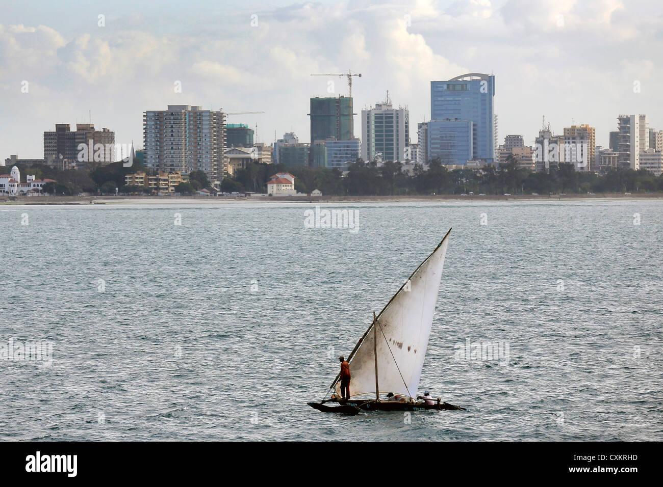 Bateau à voile traditionnel arabe (dhow) avec la capitale tanzanienne Dar es-Salaam en arrière-plan Photo Stock