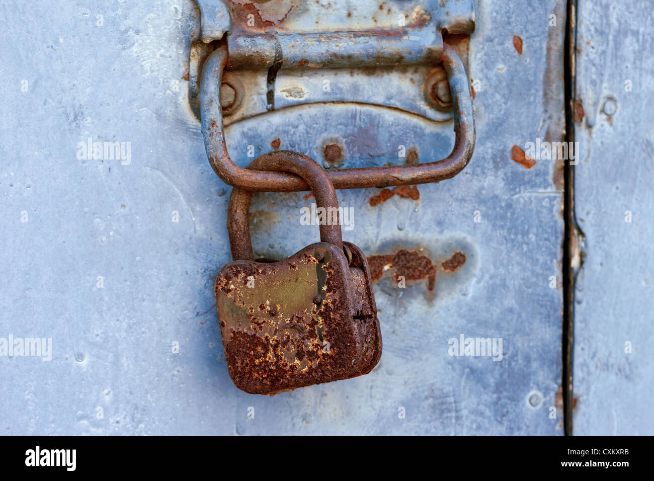 Cadenas rouillé sur une vieille porte métallique Banque D'Images