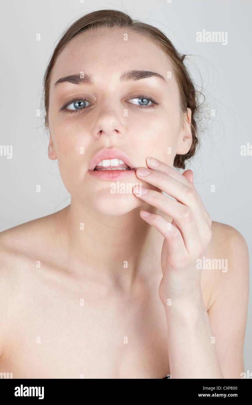 Femme regardant son visage dans le miroir Photo Stock