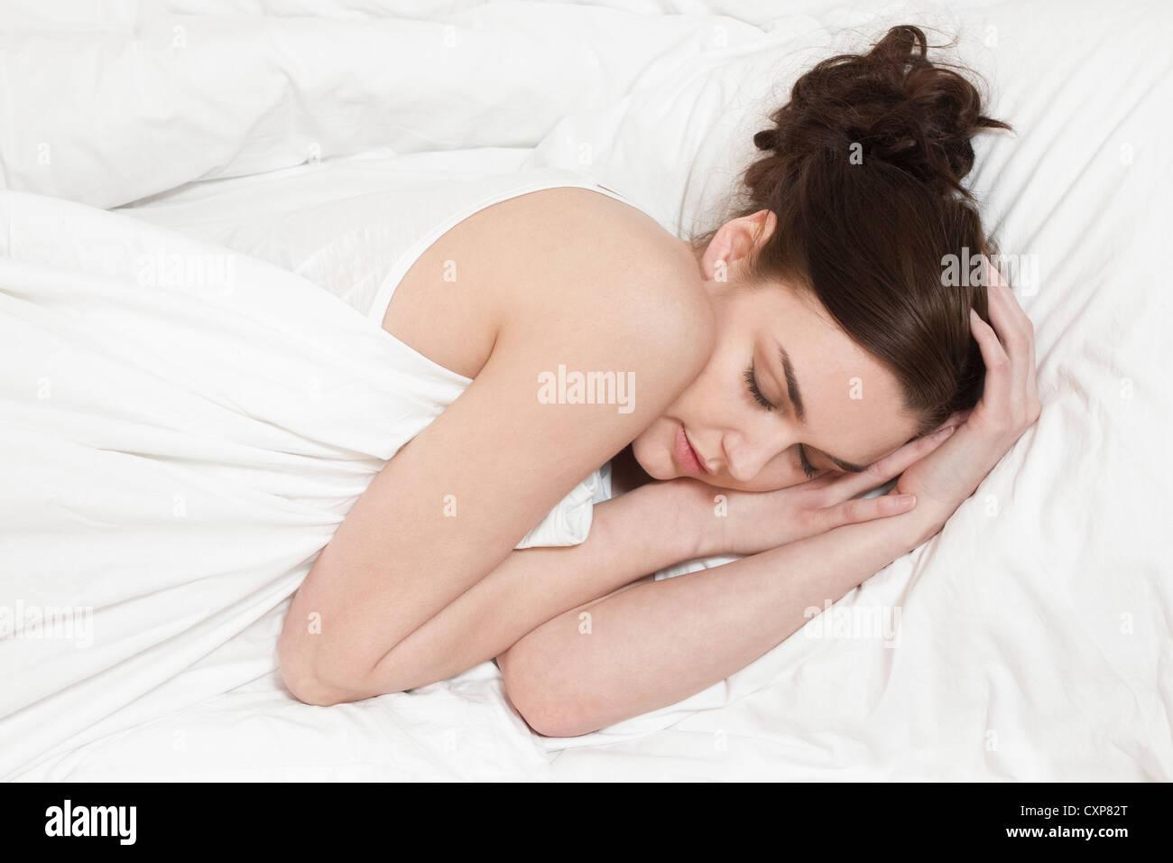 Belle jeune femme dormir seul dans le lit Photo Stock